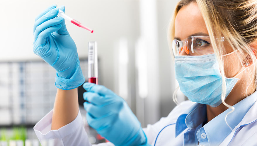 lab technician dropping blood into test tube